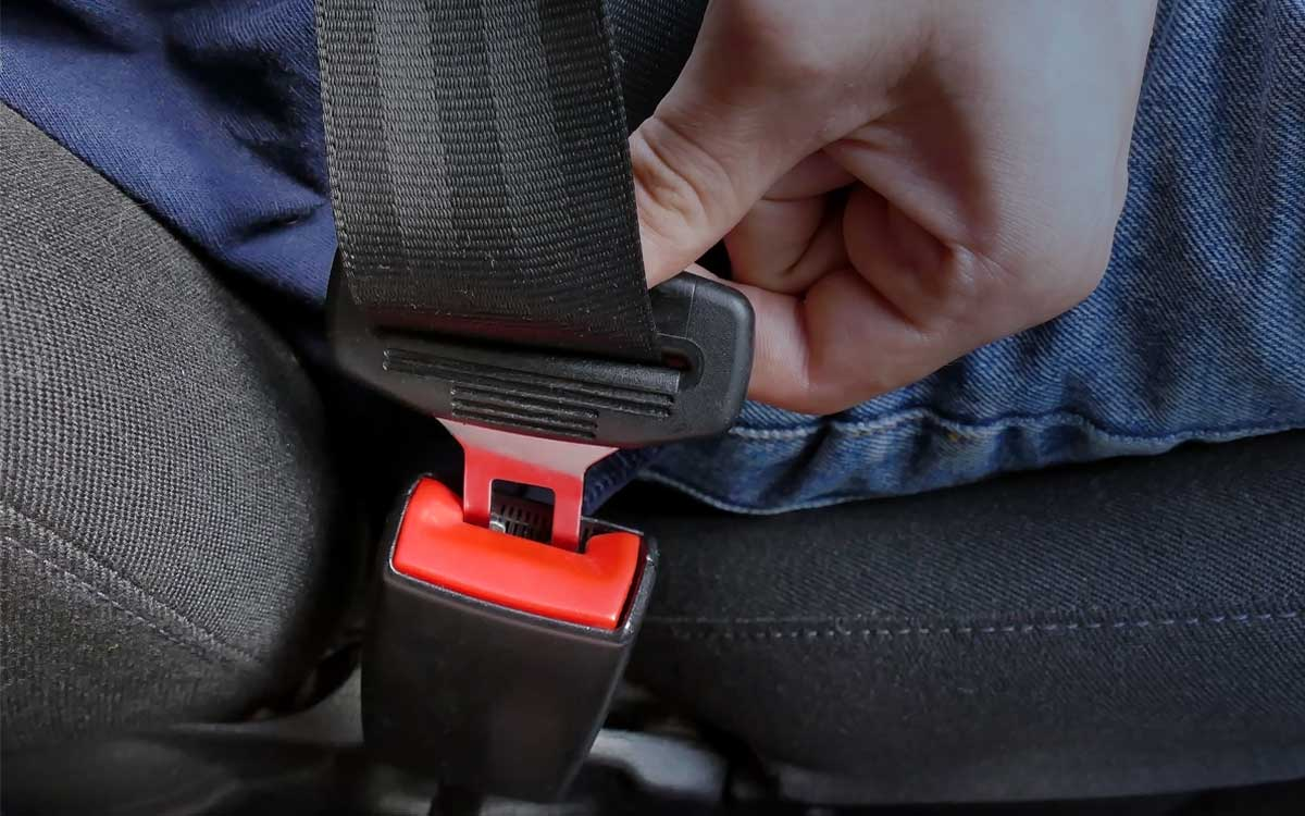 Picture of a person buckling his or her seat belt