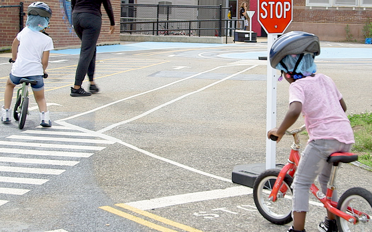 Children riding a bike, stopped at a stop sign