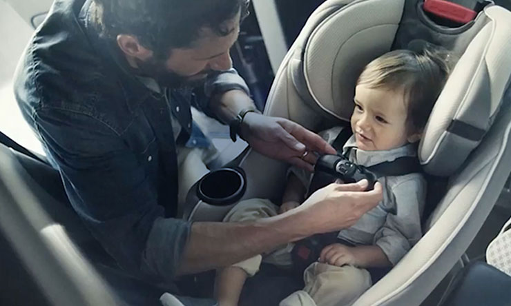 Photo of infant in being buckled into car seat by parent