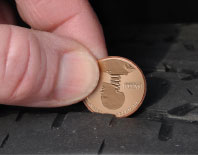 Photo of a penny being used to measure tire tread