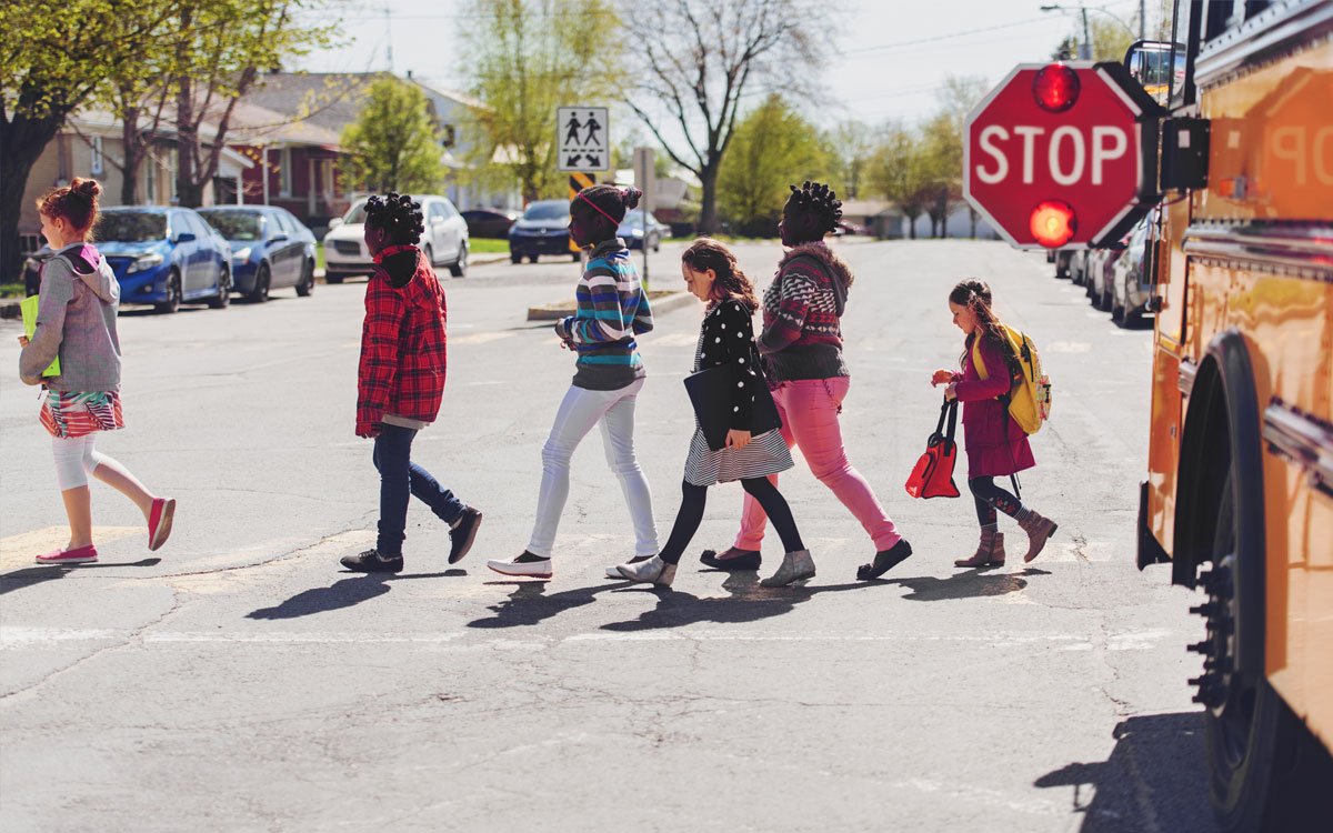 Students crossing in front of a school bus, stop sign out