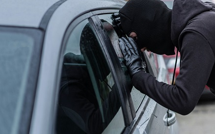 image of masked person looking into a vehicle side window