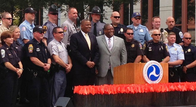 NHTSA Administrator David Strickland, DOT Secretary Foxx, and law enforcement officers stand behind a bed of more than 3,000 red flags that represent other victims who were killed in alcohol-related crahses in 2011.